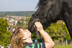 Beautiful young woman with her black horse Stock Photo