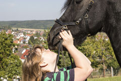 Beautiful young woman with her black horse Royalty Free Stock Images