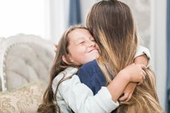 Beautiful young woman and her charming little daughter are hugging and smiling royalty free stock photos