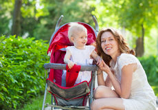 Beautiful young woman with her child in a baby carriage. Beautiful young women with her child in a baby carriage in the park Stock Photography