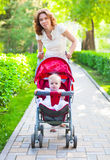 Beautiful young woman with her child in a baby carriage. Beautiful young women with her child in a baby carriage in the park Royalty Free Stock Images