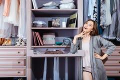 Beautiful young woman in her closet. Beautiful young smiling woman choosing at her closet royalty free stock photos