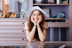 Beautiful young woman in her closet. Beautiful young smiling woman in her closet wearing hat stock photo