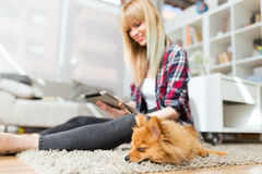 Beautiful young woman with her dog using digital tablet at home. Royalty Free Stock Photos