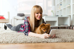 Beautiful young woman with her dog using mobile phone at home. Stock Image