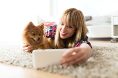 Beautiful young woman with her dog using mobile phone at home. Royalty Free Stock Images