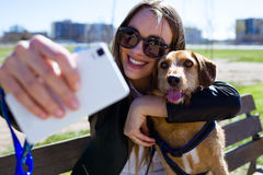 Beautiful young woman with her dog using mobile phone. stock photography