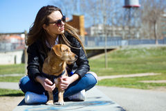 Beautiful young woman with her dog walking in the park. Stock Photos