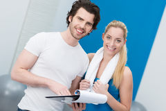 Beautiful young woman with her gym instructor Royalty Free Stock Photos