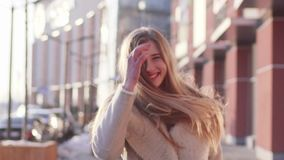Beautiful young woman with her hair loose walking past a modern building turning to the camera and smiling. stock video footage