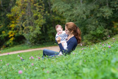 Beautiful young woman and her little bay relaxing in the garden Royalty Free Stock Photography