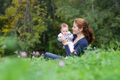 Beautiful young woman and her little bay relaxing in the garden Royalty Free Stock Photos