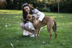 Young woman with her dog in the park. A beautiful young woman with her pet dog in the park enjoying the day Royalty Free Stock Photo