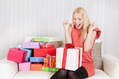 Beautiful young woman with her presents. On the sofa Royalty Free Stock Photography