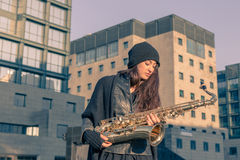 Beautiful young woman with her saxophone Royalty Free Stock Photos