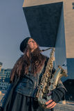 Beautiful young woman with her saxophone Royalty Free Stock Image