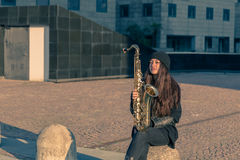Beautiful young woman with her saxophone Royalty Free Stock Images