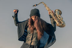 Beautiful young woman with her saxophone Royalty Free Stock Photography