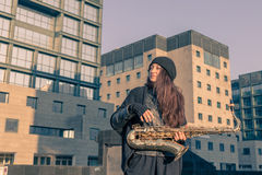 Beautiful young woman with her saxophone Stock Image