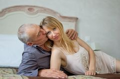 Beautiful Young Woman with Her Senior Lover Lying on the Bed. Man Kissing His Girlfriend.Portrait of Happy Lovely Couple. With Age Difference Royalty Free Stock Photography