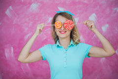 Beautiful young woman hides eyes with sweet lollipops over pink. Background. Holiday concept Royalty Free Stock Photo
