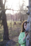 Beautiful young woman hiding behind a tree Stock Photography
