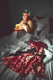Beautiful young woman hiding under the blanket and eating cookie Royalty Free Stock Images