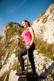 Beautiful young woman hiking in mountains on a sunny summer afte Stock Image