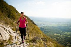 Beautiful young woman hiking in mountains on a sunny summer afte Royalty Free Stock Image
