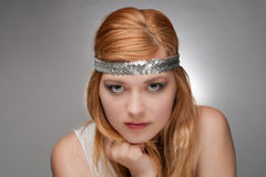 Redhaired hippie girl. Portrait of an attractive young teenage girl with red hair and silver headband on gray background Stock Images