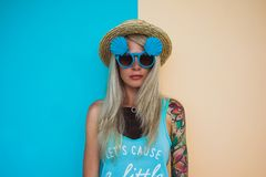 Beautiful young woman hipster with a tattoo in sunglasses and a hat on a bright coloured background. Beach style Royalty Free Stock Photo