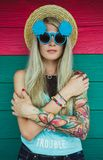 Beautiful young woman hipster with a tattoo in sunglasses and a hat on a bright coloured background. Beach style Stock Images