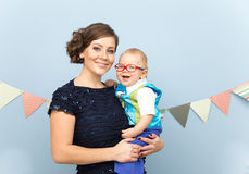 Beautiful young woman hold laughing baby boy on her hands. Beautiful young women hold laughing baby boy with glasses on her hands Stock Photos