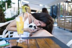 Young woman with her dog in cafe bar stock photo