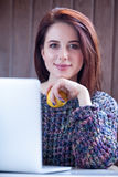 Beautiful young woman holding apple near her laptop on the wonde Royalty Free Stock Images