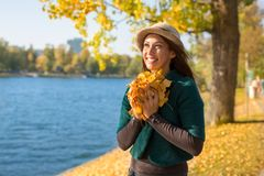 Beautiful young woman holding autumn leaves in her hand while sm stock image