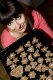 Beautiful young woman holding baking tray with gingerbread cookies Royalty Free Stock Images