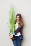 Beautiful young woman holding big green plant Royalty Free Stock Images