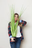Beautiful young woman holding big green plant Royalty Free Stock Photos