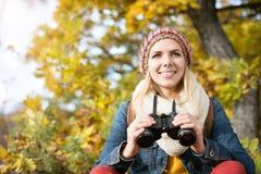 Beautiful young woman holding binoculars, colorful sunny autumn. Beautiful young woman holding binoculars against colorful sunny autumn forest Stock Images
