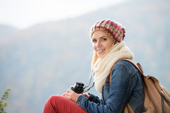 Beautiful young woman holding binoculars, colorful sunny autumn. Beautiful young woman holding binoculars against colorful sunny autumn forest Royalty Free Stock Images