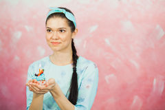 Beautiful young woman holding birthday cupcake and making wish. Celebrating anniversary concept, pink background, copy space Royalty Free Stock Images