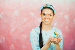 Beautiful young woman holding birthday cupcake and making wish. Celebrating anniversary concept, pink background, copy space Stock Image