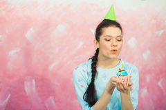Beautiful young woman holding birthday cupcake and making wish. Beautiful young woman in holiday cap holding birthday cupcake and making wish and blowing candle Stock Photography