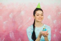 Beautiful young woman holding birthday cupcake and making wish. Beautiful young woman in holiday cap holding birthday cupcake and making wish. Celebrating Stock Image