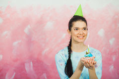 Beautiful young woman holding birthday cupcake and making wish. Beautiful young woman in holiday cap holding birthday cupcake and making wish. Celebrating Royalty Free Stock Images