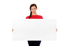 Beautiful young woman holding a blank banner.  Stock Images