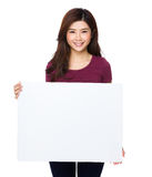 Beautiful young woman holding blank billboard Stock Photo