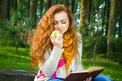 Beautiful young woman holding book and apple in the park Royalty Free Stock Photos