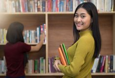 Beautiful young woman holding books in her hand and smiling at c Royalty Free Stock Images